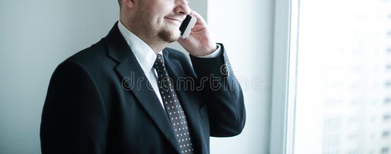 Όμορφος σκεπτικός επιχειρηματίας χρησιμοποιώντας το smartphoone και κοιτάζοντας μέσω του παραθύρου στο γραφείο στοκ εικόνες με δικαίωμα ελεύθερης χρήσης