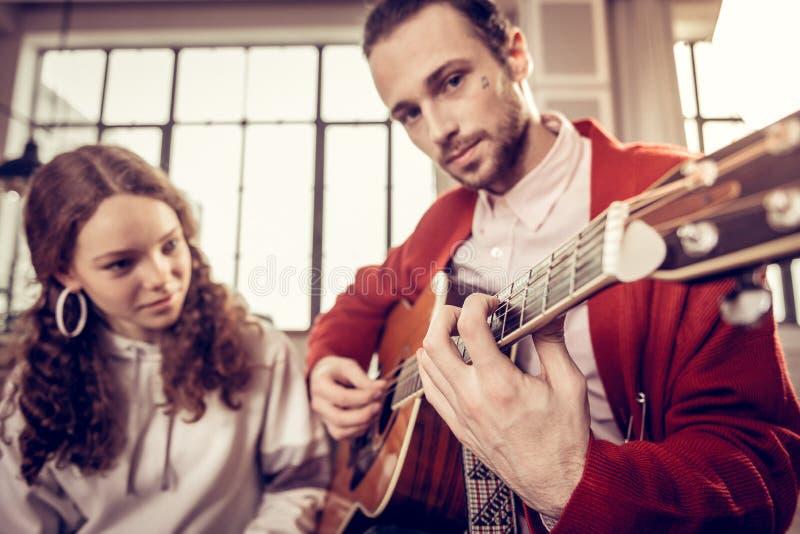 Όμορφος σκοτεινός-eyed παλαιότερος αδελφός που παίζει την κιθάρα για την αδελφή στοκ εικόνα με δικαίωμα ελεύθερης χρήσης