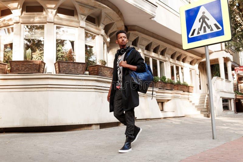 Όμορφος σπουδαστής έξω από το περπάτημα στην οδό, στα περιστασιακά ενδύματα με το σακίδιο πλάτης και την κάσκα, κοντά στη διάβαση στοκ φωτογραφίες