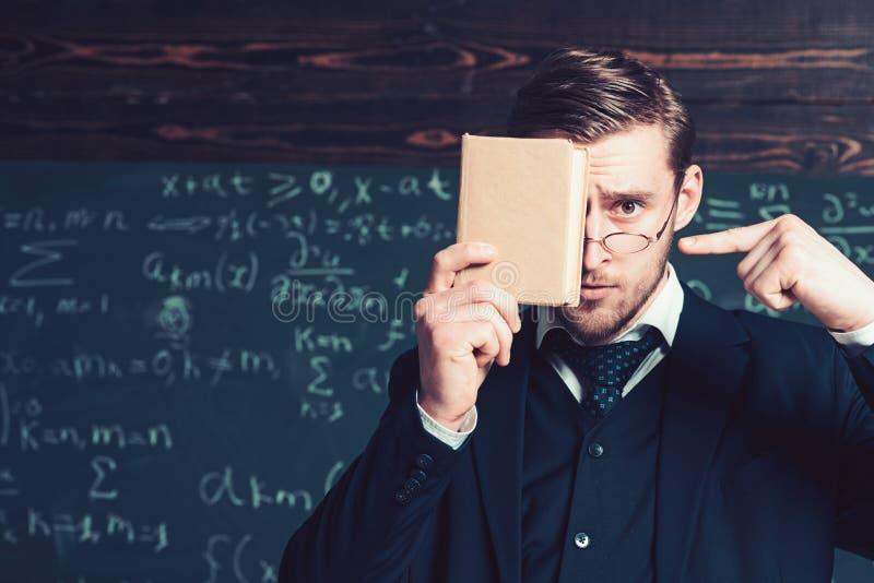 Όμορφος σπουδαστής στο κοστούμι που καλύπτει το πρόσωπό του με το βιβλίο δείχνοντας σε το με άλλο χέρι Πορτρέτο κινηματογραφήσεων στοκ εικόνες