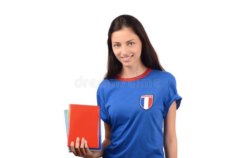 Όμορφος σπουδαστής με τη σημαία της Γαλλίας στα μπλε βιβλία εκμετάλλευσης μπλουζών, κενό κόκκινο βιβλίο κάλυψης στοκ εικόνα με δικαίωμα ελεύθερης χρήσης