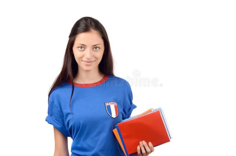 Όμορφος σπουδαστής με τη σημαία της Γαλλίας στα μπλε βιβλία εκμετάλλευσης μπλουζών, κενό κόκκινο βιβλίο κάλυψης στοκ φωτογραφία