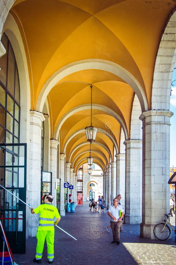 Όμορφος σταθμός στην Πίζα με τους άσπρους στυλοβάτες και τις κίτρινες αψίδες, με τους εργαζόμενους καθαριστές και τους τουρίστες, στοκ φωτογραφία με δικαίωμα ελεύθερης χρήσης
