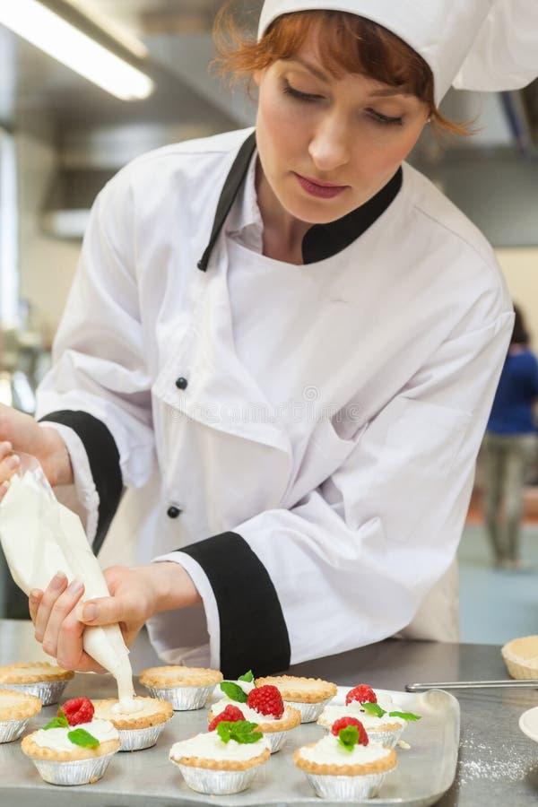 Όμορφος συγκεντρωμένος επικεφαλής αρχιμάγειρας που προετοιμάζει το επιδόρπιο στοκ εικόνα