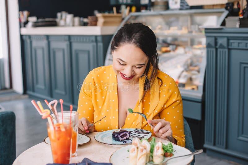 Όμορφος συν τη γυναίκα μεγέθους που τρώει το επιδόρπιο στον καφέ στοκ εικόνες