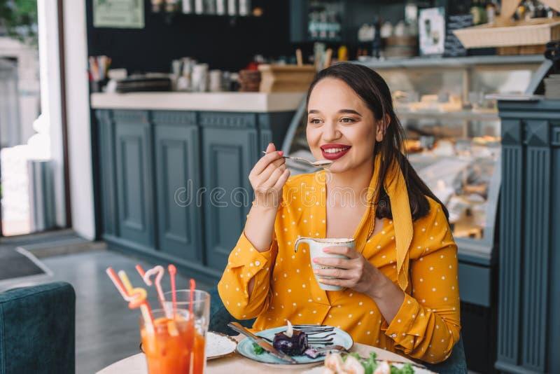 Όμορφος συν τη γυναίκα μεγέθους που τρώει το επιδόρπιο στον καφέ στοκ φωτογραφία