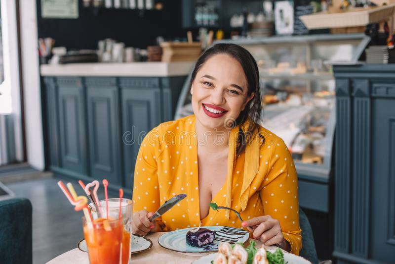 Όμορφος συν τη γυναίκα μεγέθους που τρώει το επιδόρπιο στον καφέ στοκ φωτογραφία με δικαίωμα ελεύθερης χρήσης