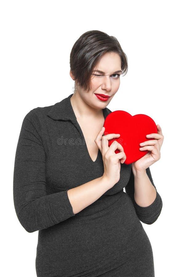 Όμορφος συν τη γυναίκα μεγέθους το κόκκινο κλείσιμο του ματιού καρδιών που απομονώνεται με στοκ φωτογραφία