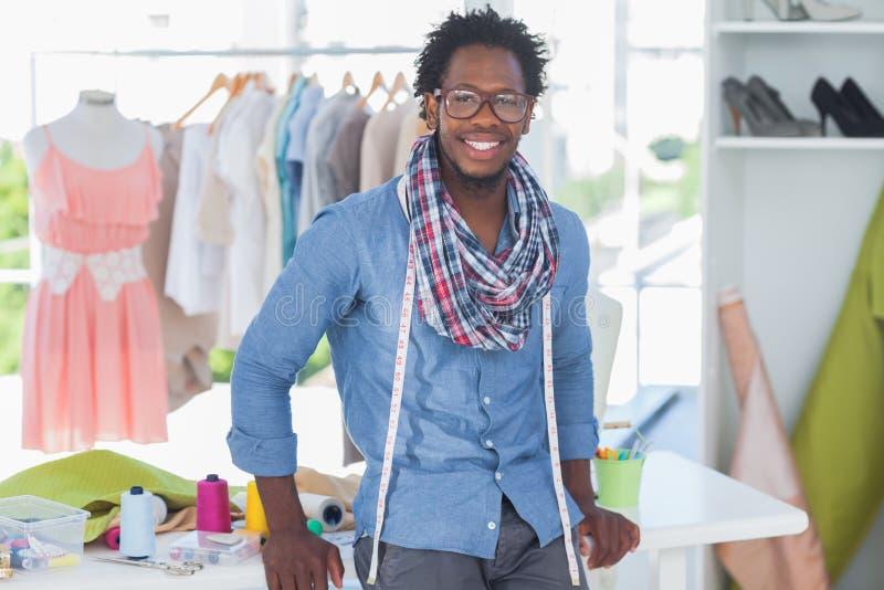 Όμορφος σχεδιαστής μόδας που κλίνει στο γραφείο στοκ εικόνα με δικαίωμα ελεύθερης χρήσης