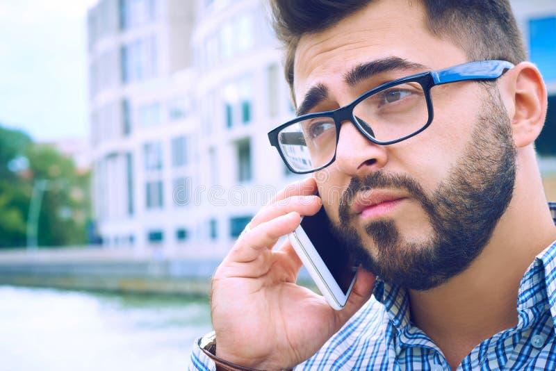 Όμορφος σύγχρονος επιχειρηματίας hipster στα γυαλιά με τη γενειάδα που περπατά στην πόλη και που καλεί το κινητό τηλέφωνο στοκ εικόνες με δικαίωμα ελεύθερης χρήσης