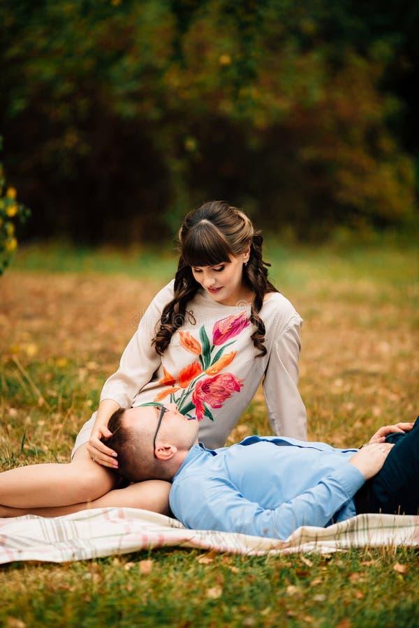 Όμορφος σύζυγος που βρίσκεται στο πόδι της νέας έγκυου όμορφης γυναίκας του στο πάρκο στοκ εικόνα