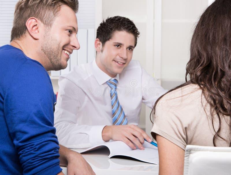 Όμορφος σύμβουλος στο πουκάμισο και δεσμός με ένα ζεύγος στο γραφείο. στοκ φωτογραφία με δικαίωμα ελεύθερης χρήσης