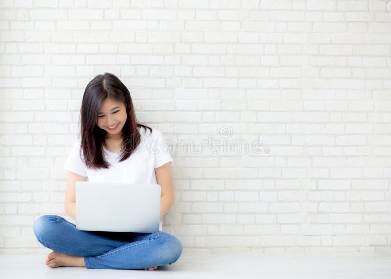 Όμορφος της ασιατικής νέας γυναίκας πορτρέτου που απασχολείται στη σε απευθείας σύνδεση συνεδρίαση lap-top στο υπόβαθρο τσιμέντου στοκ εικόνα με δικαίωμα ελεύθερης χρήσης