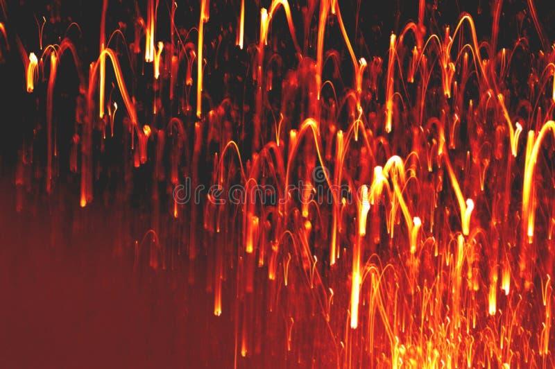 Όμορφος το εορταστικό υπόβαθρο στα χρυσά και κόκκινα χρώματα, όπως σπινθήρες της πυρκαγιάς στοκ εικόνες