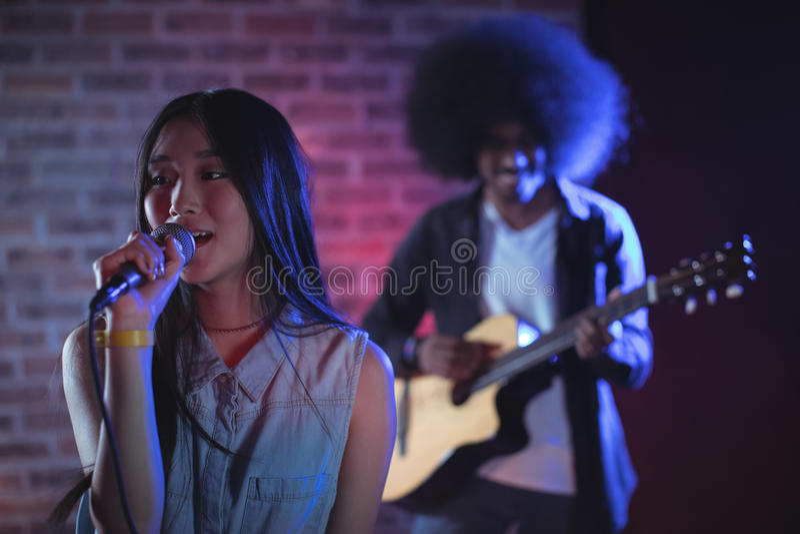 Όμορφος τραγουδιστής με τον κιθαρίστα που αποδίδει στο νυχτερινό κέντρο διασκέδασης στοκ φωτογραφία με δικαίωμα ελεύθερης χρήσης