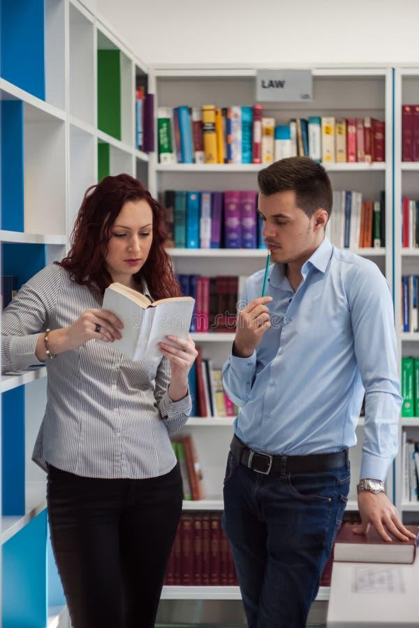 Όμορφος τύπος και όμορφο redhead κορίτσι που μελετούν στη βιβλιοθήκη στοκ εικόνα με δικαίωμα ελεύθερης χρήσης
