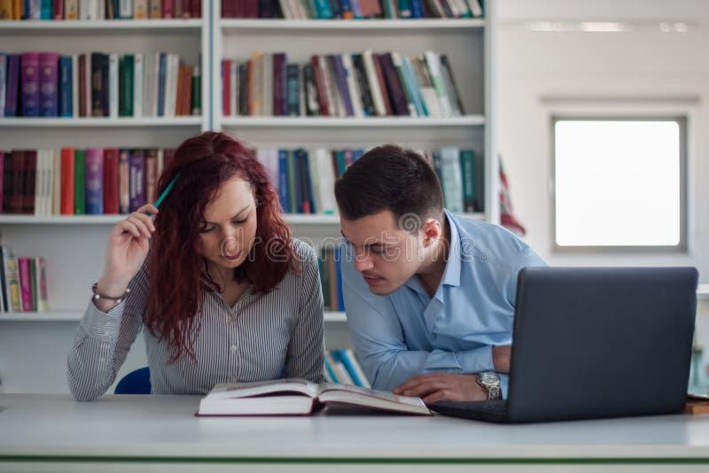 Όμορφος τύπος και όμορφο redhead κορίτσι που μελετούν στη βιβλιοθήκη στοκ φωτογραφία