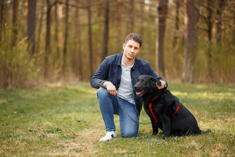 Όμορφος τύπος με ένα μαύρο σκυλί που περπατά στο πάρκο στοκ φωτογραφία