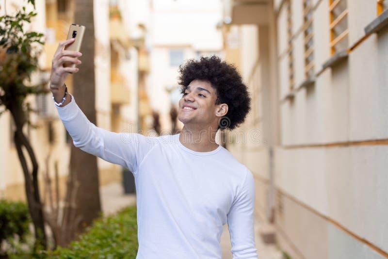 Όμορφος τύπος που εξετάζει τον κινητό στοκ φωτογραφία