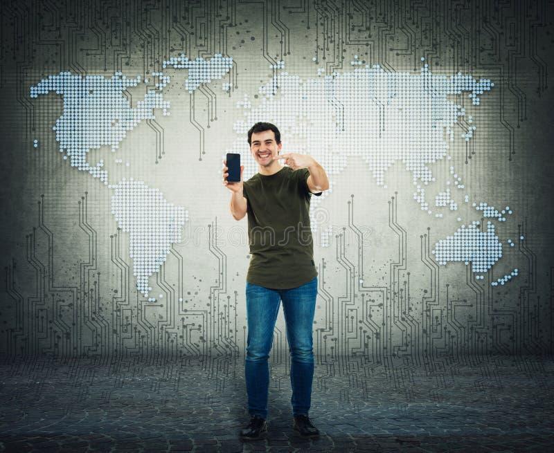 Όμορφος τύπος που παρουσιάζει ένα καθιερώνον τη μόδα smartphone Θετικό χαμογελώντας άτομο που παρουσιάζει νέο τηλέφωνο πέρα από τ στοκ φωτογραφία με δικαίωμα ελεύθερης χρήσης