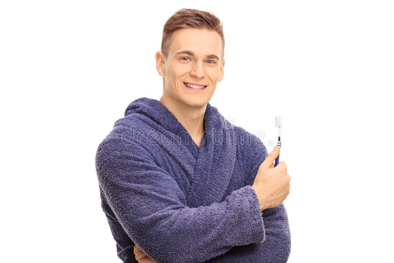 Όμορφος τύπος σε ένα μπουρνούζι που κρατά μια οδοντόβουρτσα στοκ εικόνα