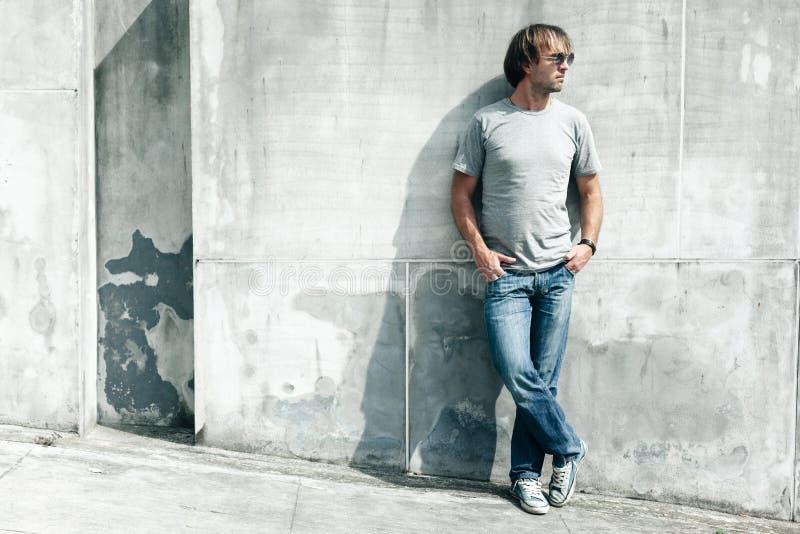 Όμορφος τύπος στην γκρίζα μπλούζα πέρα από τον τοίχο οδών στοκ εικόνες