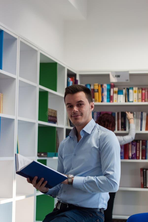 Όμορφος τύπος brunette που κοιτάζει μακριά και που στέκεται δίπλα στο βιβλίο στοκ εικόνα με δικαίωμα ελεύθερης χρήσης