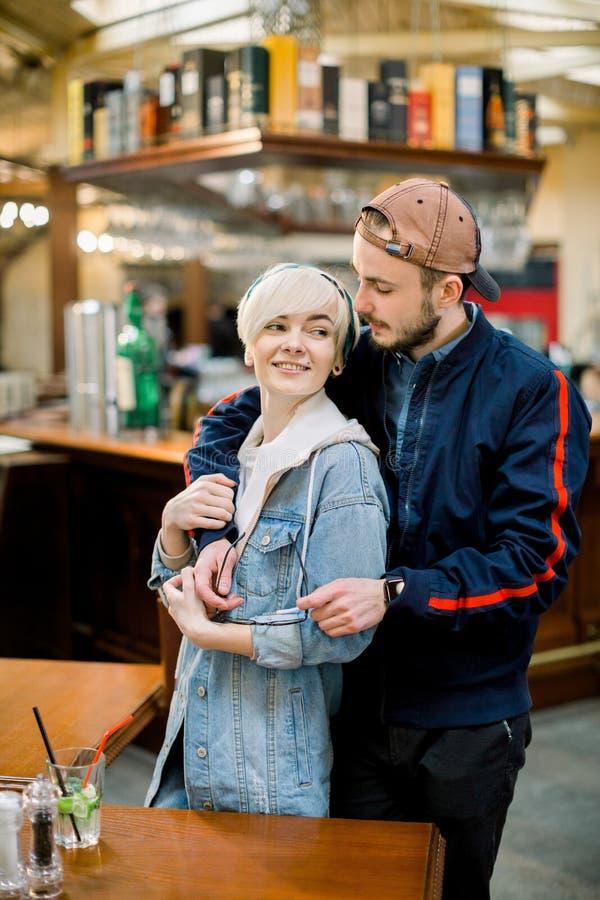 Όμορφος φίλος που αγκαλιάζει τη χαμογελώντας φίλη κατά τη διάρκεια της ημερομηνίας στον καφέ Χαμογελώντας δημιουργικό ζεύγος που  στοκ εικόνα με δικαίωμα ελεύθερης χρήσης