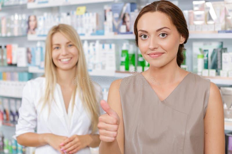 Όμορφος φαρμακοποιός κοριτσιών που βοηθά έναν πελάτη στοκ φωτογραφία με δικαίωμα ελεύθερης χρήσης