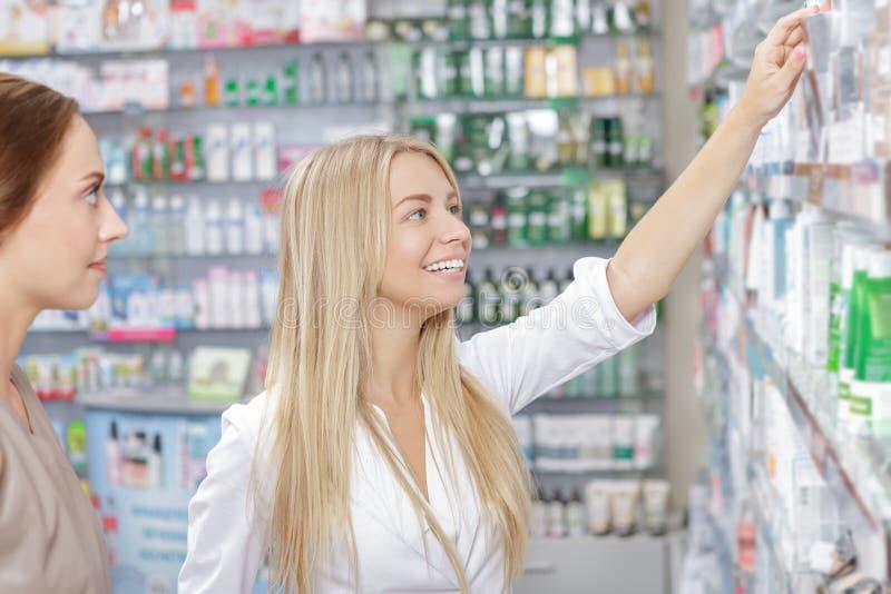 Όμορφος φαρμακοποιός κοριτσιών που βοηθά έναν πελάτη στοκ εικόνες