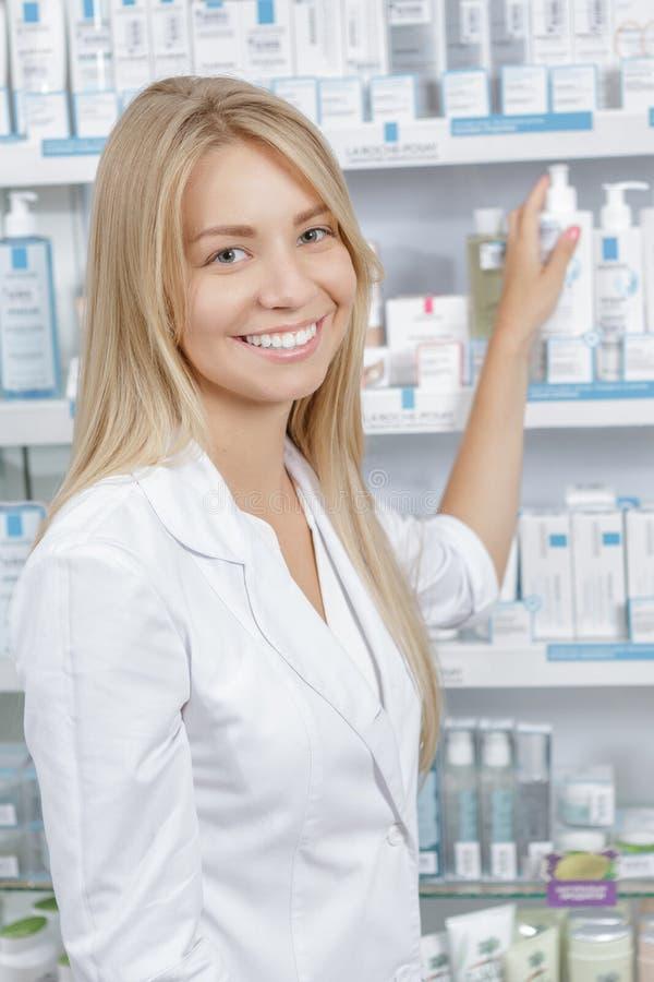 Όμορφος φαρμακοποιός που επιλέγει το προϊόν στοκ εικόνα