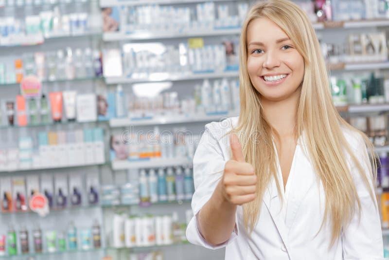 Όμορφος φαρμακοποιός που στέκεται σε ένα φαρμακείο στοκ εικόνες