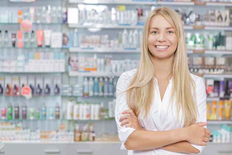 Όμορφος φαρμακοποιός που στέκεται σε ένα φαρμακείο στοκ φωτογραφίες