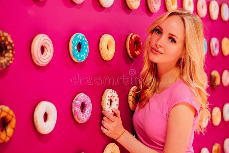 Όμορφος φωνάξτε το ξανθό κορίτσι στη ρόδινη κινηματογράφηση σε πρώτο πλάνο στο ρόδινο doughnut υπόβαθρο στοκ εικόνες