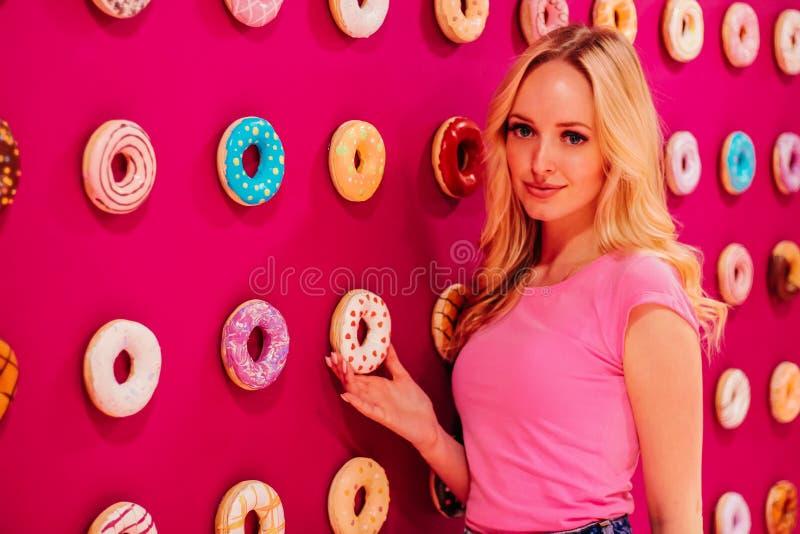 Όμορφος φωνάξτε το ξανθό κορίτσι στη ρόδινη κινηματογράφηση σε πρώτο πλάνο στο ρόδινο doughnut υπόβαθρο στοκ φωτογραφία