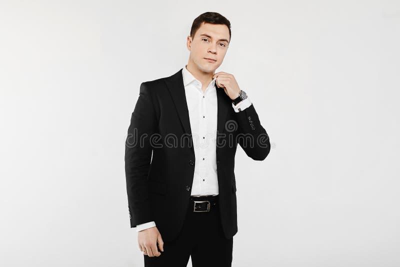 Όμορφος χαμογελώντας νέος επιχειρηματίας στο άσπρο πουκάμισο με τα μανικετόκουμπα και στο μοντέρνο μαύρο κοστούμι, που απομονώνετ στοκ εικόνα με δικαίωμα ελεύθερης χρήσης