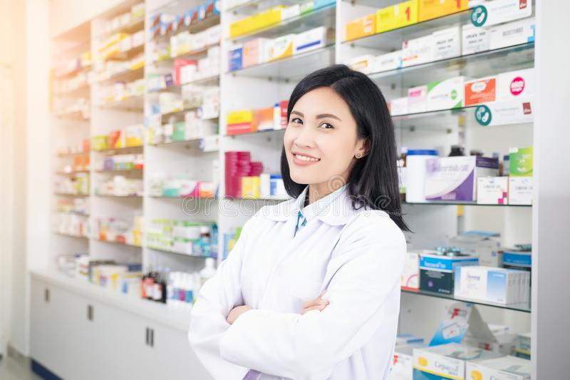Όμορφος χαμογελώντας νέος φαρμακοποιός γυναικών που κάνει την εργασία του στο φαρμακείο στοκ φωτογραφία με δικαίωμα ελεύθερης χρήσης