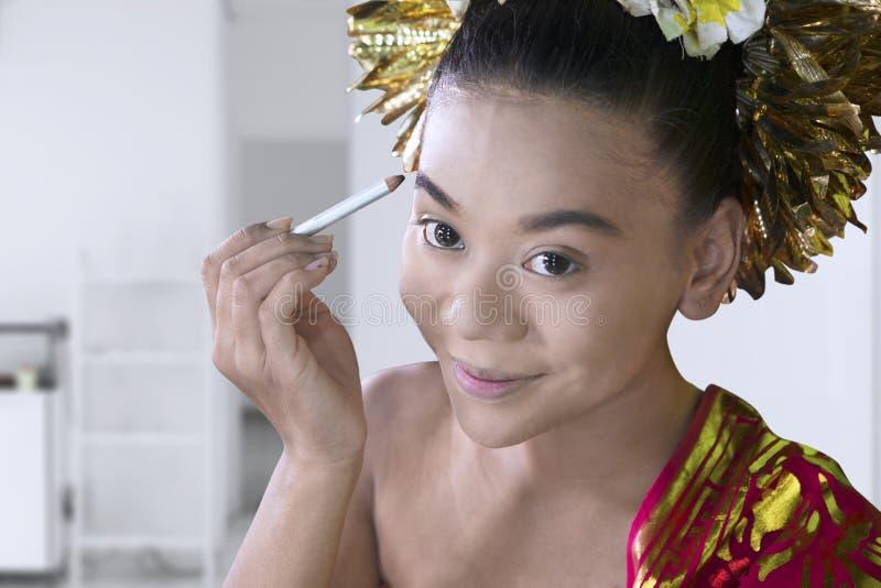 Όμορφος χορευτής που κάνει makeup με το καλλυντικό μολύβι στοκ φωτογραφία με δικαίωμα ελεύθερης χρήσης