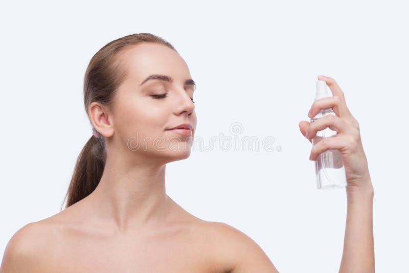 Όμορφος ψεκασμός γυναικών στο πρόσωπο που απομονώνεται στο λευκό στοκ φωτογραφίες με δικαίωμα ελεύθερης χρήσης