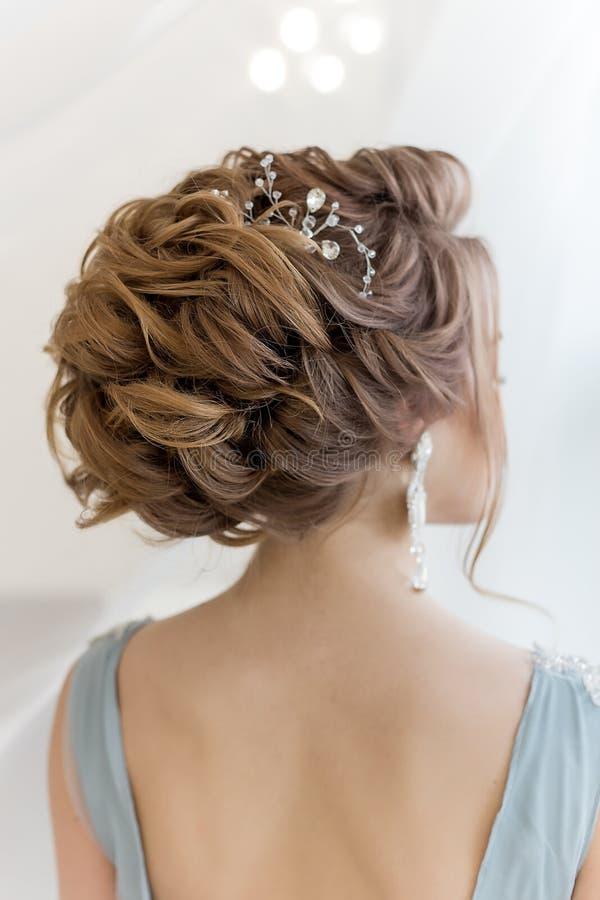 Όμορφος όγκος hairstyle για μια νύφη σε ένα ευγενές μπλε ελαφρύ φόρεμα με τα μεγάλα σκουλαρίκια και το στολισμό στην τρίχα στοκ εικόνες