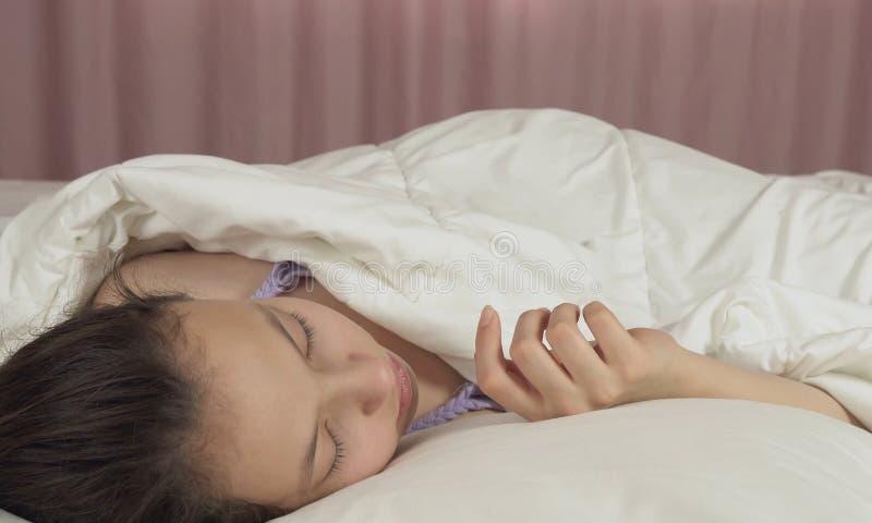 Όμορφος ύπνος κοριτσιών εφήβων γλυκά στο κρεβάτι στοκ φωτογραφία