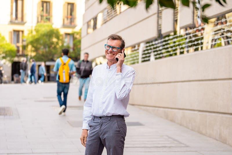 Όμορφος ώριμος δημιουργικός ανεξάρτητος επιχειρηματίας που μιλά στο κινητό τηλέφωνο και που χαμογελά περπατώντας την υπαίθρια αστ στοκ φωτογραφία