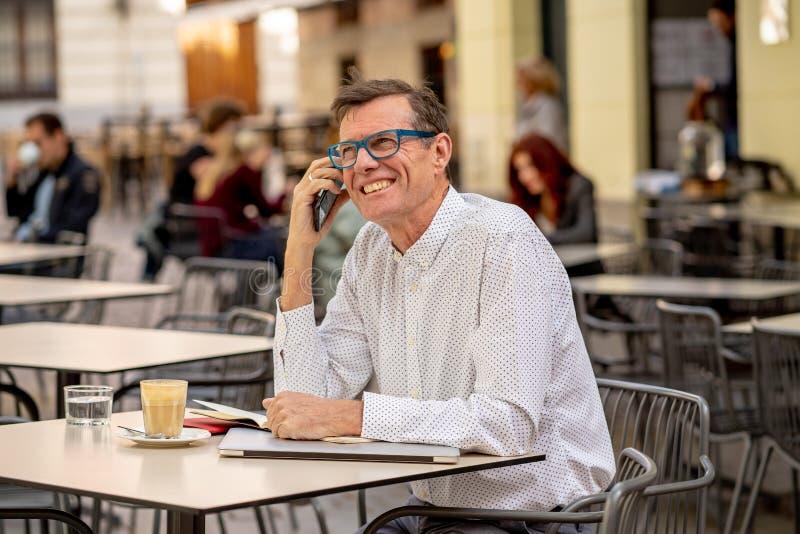 Όμορφος ώριμος δημιουργικός ανεξάρτητος επιχειρηματίας που μιλά στο κινητό τηλέφωνο και που χαμογελά περπατώντας την υπαίθρια αστ στοκ εικόνες