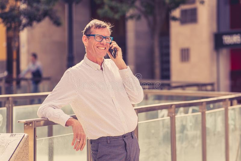 Όμορφος ώριμος δημιουργικός ανεξάρτητος επιχειρηματίας που μιλά στο κινητό τηλέφωνο και που χαμογελά περπατώντας την υπαίθρια αστ στοκ φωτογραφίες με δικαίωμα ελεύθερης χρήσης