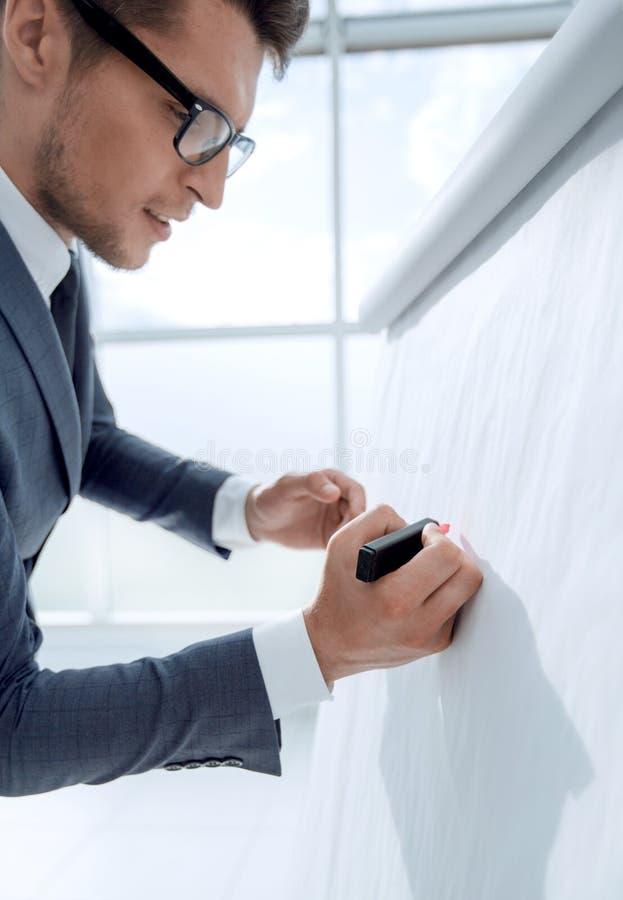 Όμορφος ώριμος επιχειρηματίας που γράφει στο κενό διάγραμμα κτυπήματος στοκ εικόνες