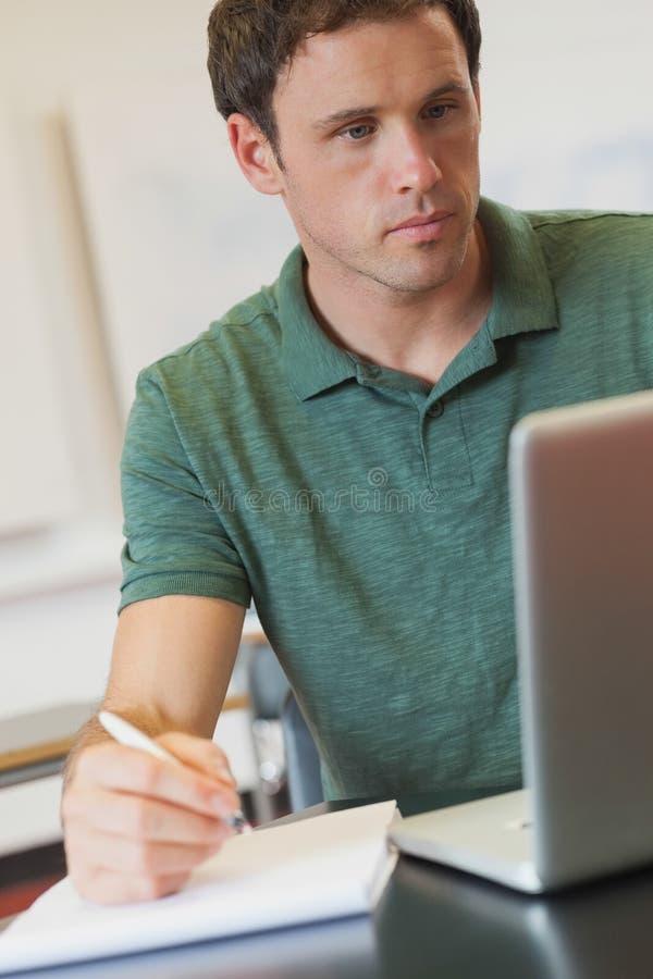 Όμορφος ώριμος σπουδαστής που χρησιμοποιεί το σημειωματάριό του για την εκμάθηση στοκ εικόνα