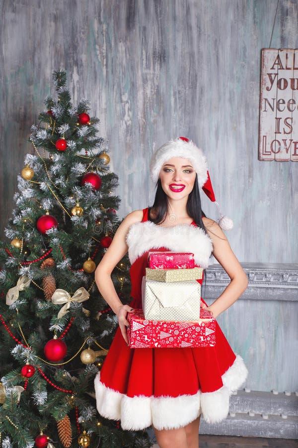 όμορφος Claus ντύνει την προκλ&eta Χαμογελώντας γυναίκα με το μεγάλο και μικρό δώρο Γυναίκες στο καπέλο φορεμάτων και santa ` s στοκ φωτογραφία με δικαίωμα ελεύθερης χρήσης