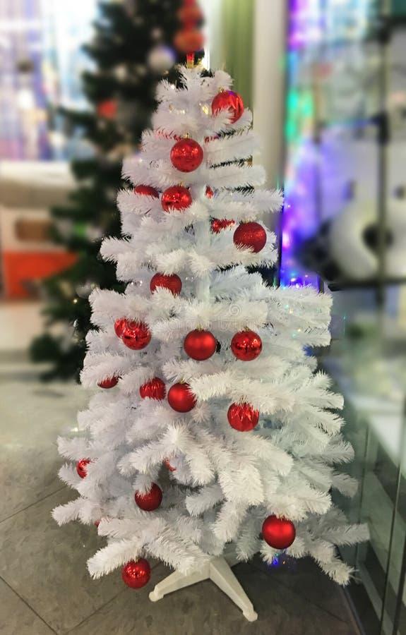 Όμορφο άσπρο χριστουγεννιάτικο δέντρο με τις κόκκινες σφαίρες στη λεωφόρο Νέα ατμόσφαιρα έτους ` s στοκ φωτογραφίες