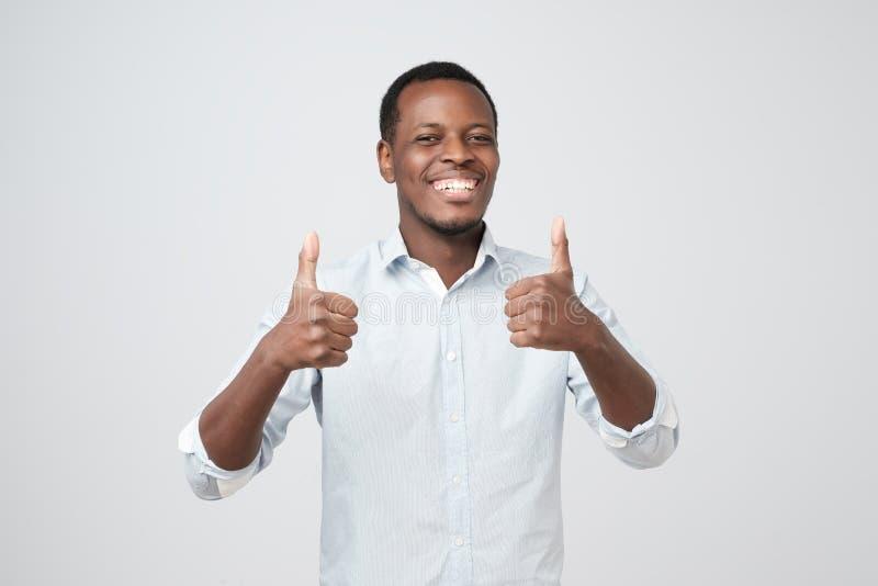 Όμορφο άτομο αφροαμερικάνων πορτρέτου που δίνει το διπλό αντίχειρα επάνω στοκ εικόνες