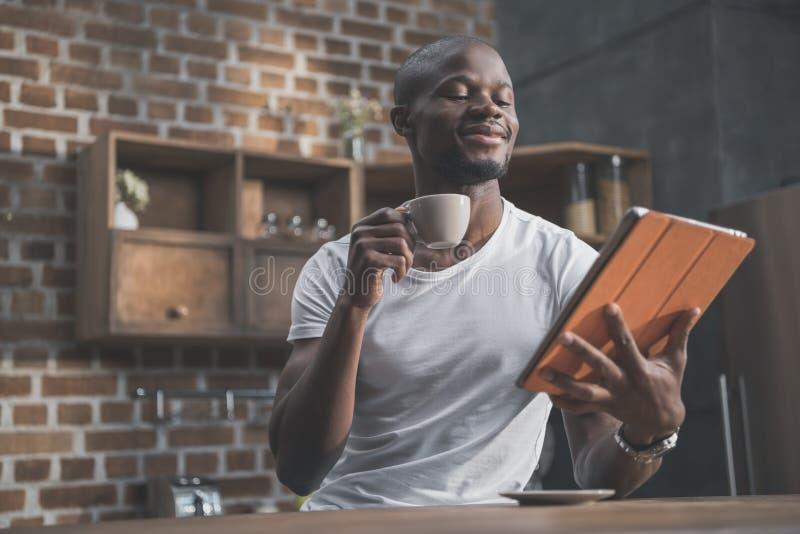 Όμορφο άτομο αφροαμερικάνων που χρησιμοποιεί την ταμπλέτα ενώ έχοντας τον καφέ πρωινού του στοκ εικόνες